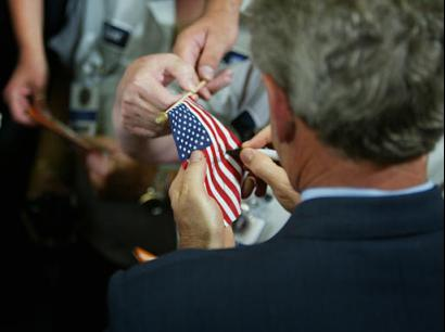 President Bush signs American flags for workers at Beaver Aerospace and Defense after speaking about jobs and economic growth in Livonia, Michigan, Thursday, July 23, 2003. President Bush, in campaign-style speeches in states vital to his re-election, sought Thursday to make sure voters give him credit for rebates heading to millions of taxpayers this week. (AP Photo/Charles Dharapak)