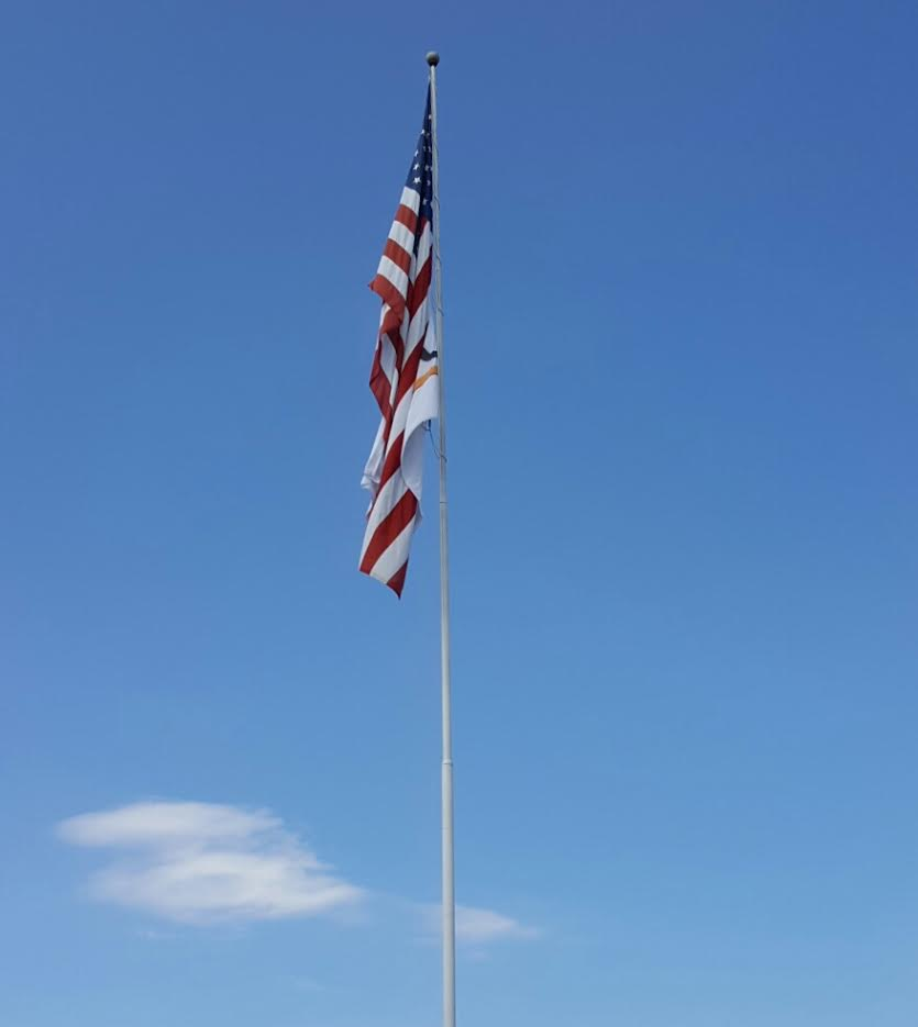 Chick Fil A and U-Haul flags flying from the same staff as the U.S. Flag
